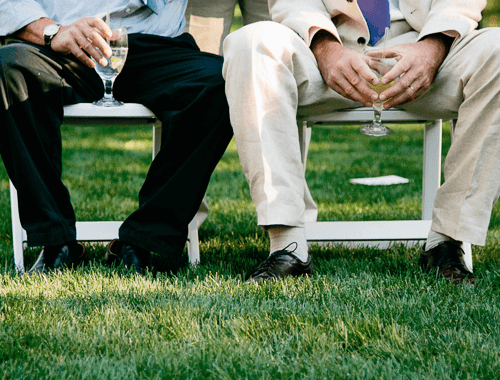 two men sitting having a glass of wine while waiting for the festivities to start