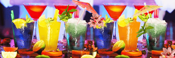 Colored glasses, martini glasses, cocktails and fruit slices
