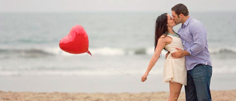 Lieutenant kisses his fiancée holding a red heart shaped balloon on the beach