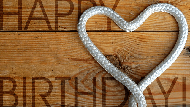 Rope heart with happy birthday on a wooden board