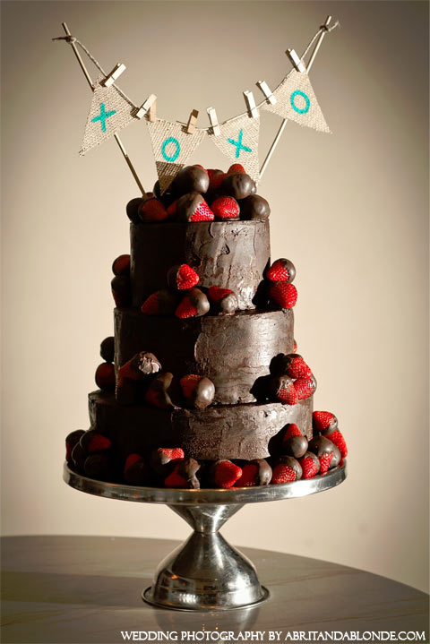 Tiered Chocolate cake with strawberry decorations and a flag banner with Tiffany Blue Xs and Os