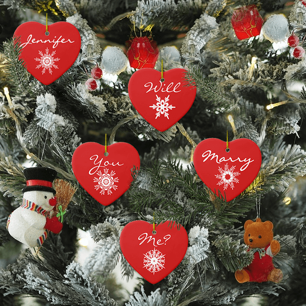 Decorated Christmas tree with proposal ornaments that say WIll You Marry Me? among other decorations