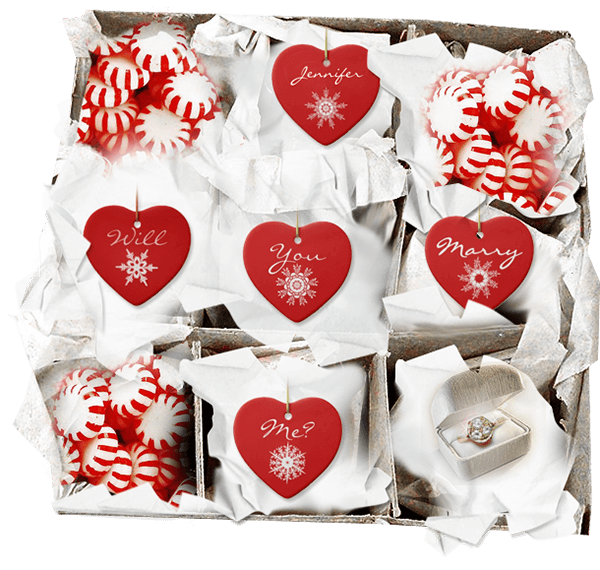 Box of red heart- shaped Christmas ornaments with Will You Marry Me and an engagment ring