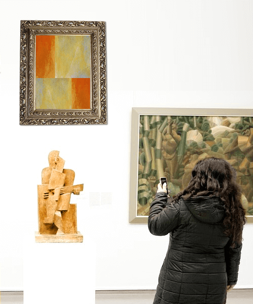 Woman in an Art Gallery taking a picture of sculpture