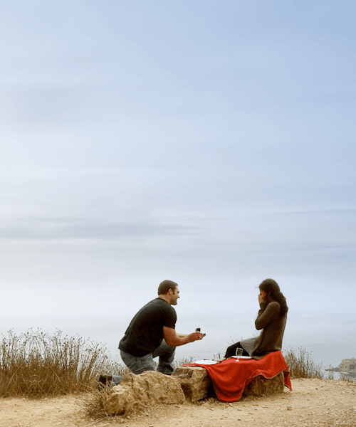 Man down on one knee proposing to his girl who is sitting on a red blanket at the top of a cliff