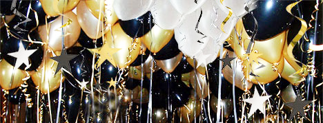 gold white and black helium filled balloons at ceiling with gold stars