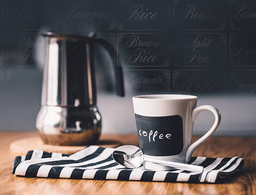coffee pot and black and white mug on a wooden kitchen counter