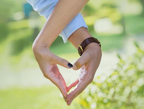 Couple forming a heart while holding hands