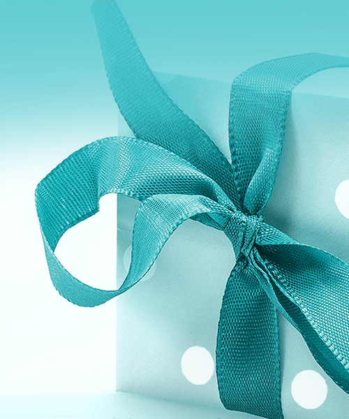 A wrapped present in tiffany blue and white polkadot paper with a matching blue ribbon