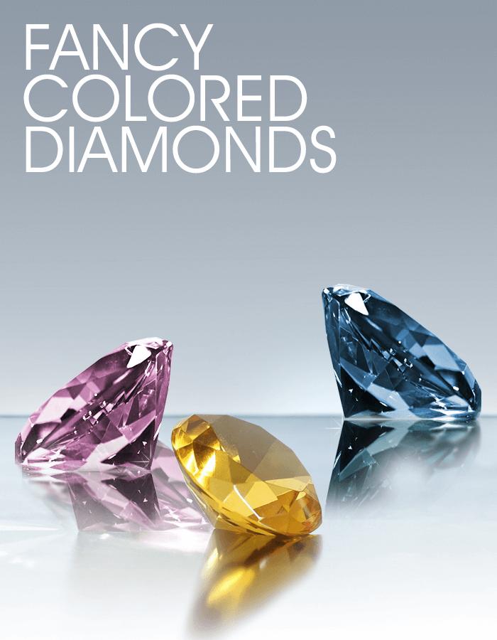 A pink diamond, canary yellow diamond and blue diamond sitting on a table
