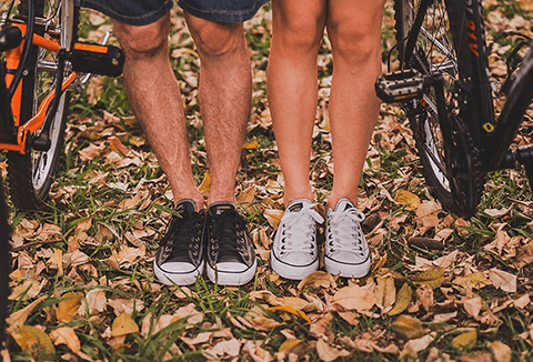 Couple in sneakers standing on autumn leaves