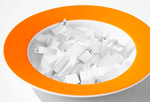 Folded pieces of paper in a bowl with an orange rim.