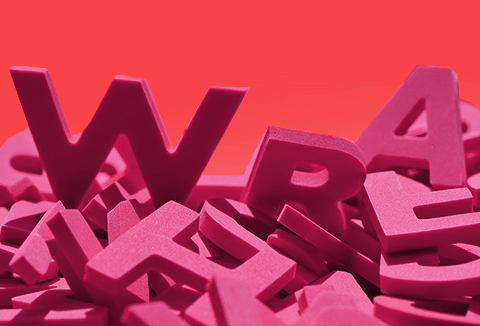Pink plastic letters in a pile on an orange background