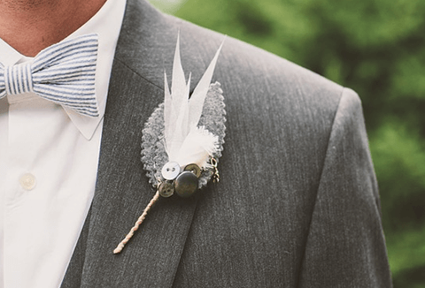 Groom's lapel with feather and button pin