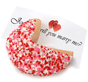 Giant Fortune cookie covered in heart shaped sprinkles with will you marry me as the fortune inside