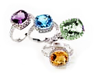 four different colored gemstone rings