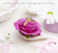 a pink rose with an engagement ring surrounded by flowers and soap