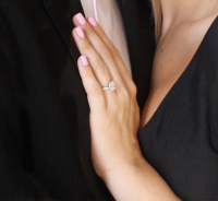 Woman resting her hand with an engagement ring on man's chest